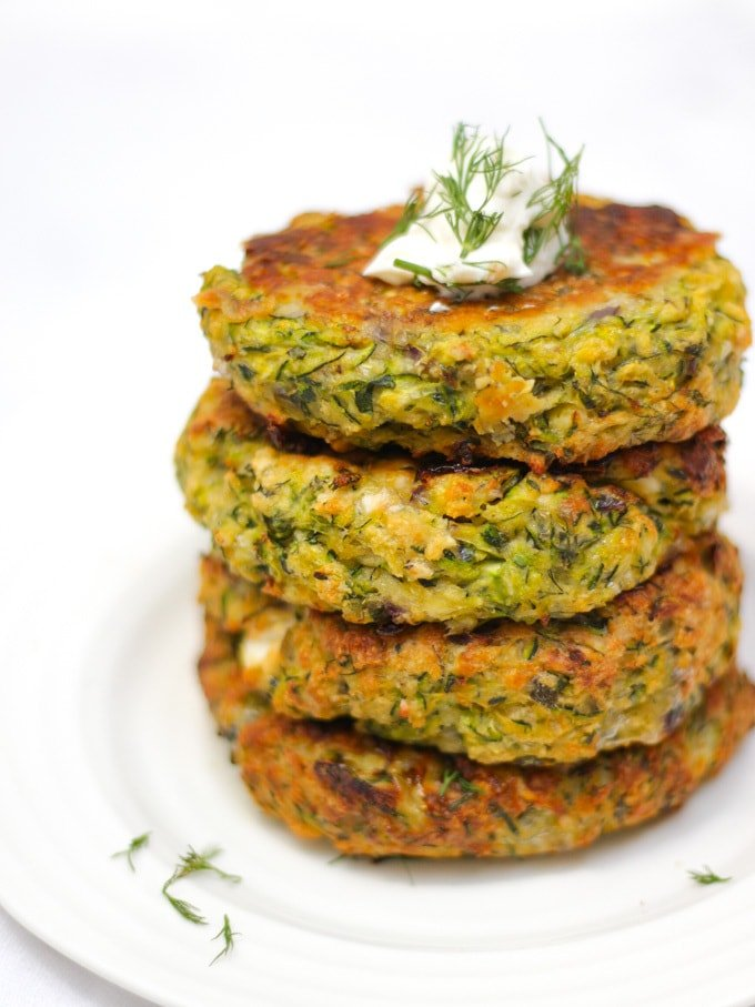 Stack of 4 courgette fritters in a pile side angle photo topped with yoghurt and dill.