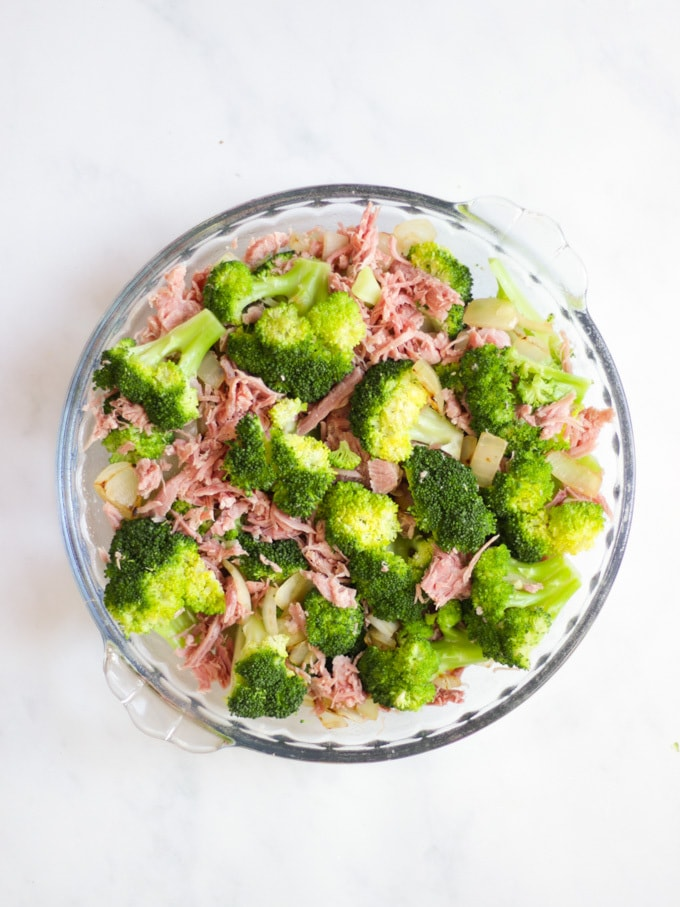 Overhead photo of broccoli and ham in a round glass dish on a white marble background for Crustless Quiche recipe.