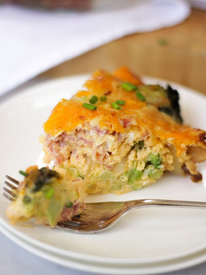 Photo of a fork and a slice of a cooked Crustless Quiche recipe with broccoli and ham on a white napkin with a wooden chopping board, chopped chives and on a white marble background.