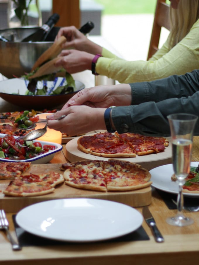 Hands reaching over table with Goodfellas Romano Frozen pizzas cooked on.