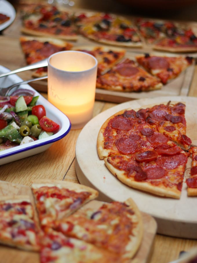 Wooden table with cooked goodfellas frozen pizzas on and a candle and salad.