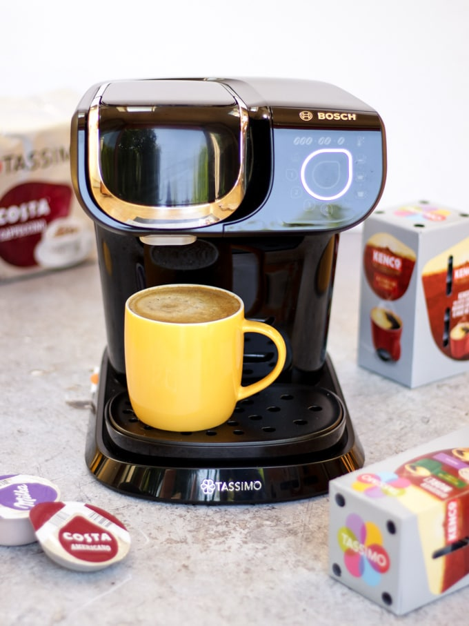 Tassimo coffee machine with yellow mug filled with coffee and coffee pods in the background for making Iced coffee recipe with salted caramel.