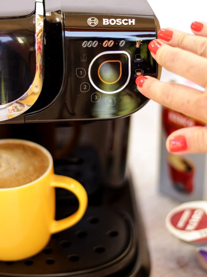 Tassimo coffee machine with finger with red fingernail pressing button with yellow mug filled with coffee and coffee pods in the background for making Iced coffee recipe with salted caramel.