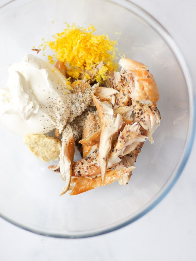 Smoked mackerel pate ingredients in a glass bowl, flaked smoked mackerel, lemon zest and cream cheese with ground pepper.
