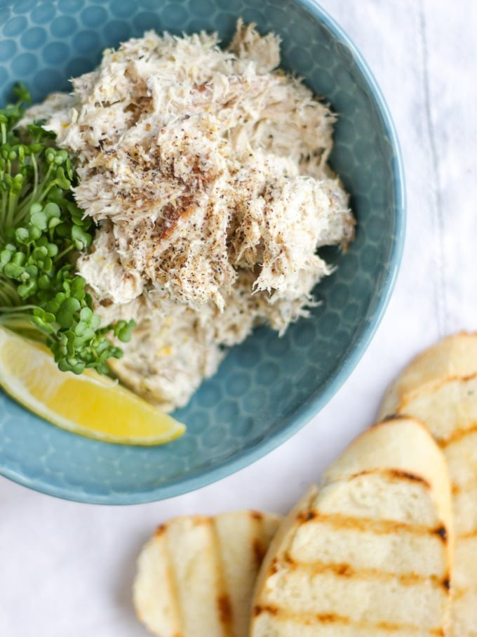 Pile of Smoked Mackerel pate in a green bowl with cress and a wedge of lemon with bread slices in the background on a white napkin. Overhead view photo.