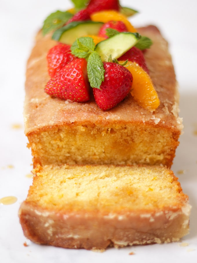 Forward photo of Orange Drizzle Cake with Pimms. Loaf cake from overhead, topped with strawberries, mint, oranges and cucumber pieces, with slice cut off the cake.