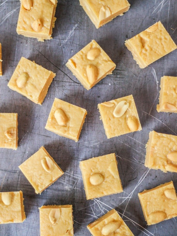 Overhead photo of microwave peanut butter fudge cubes with salted peanuts on top on grey background.