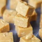 Overhead angled photo of pile of microwave peanut butter fudge cubes with salted peanuts on top on grey background.