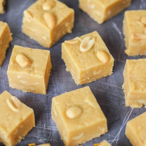 Overhead angled photo of microwave peanut butter fudge cubes with salted peanuts on top on grey background.