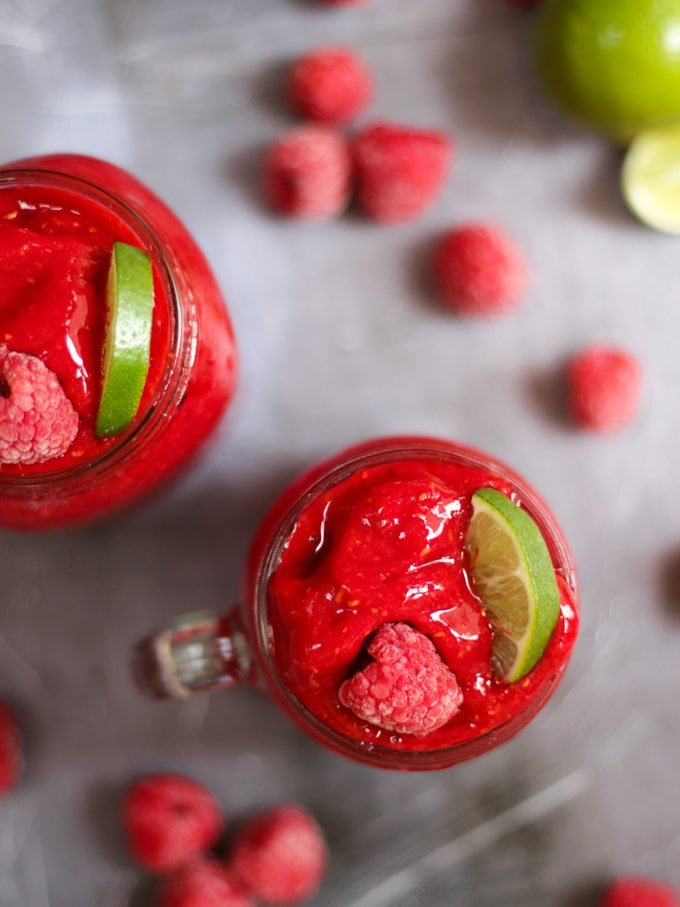 Overhead photo of raspberry gin frozen cocktails. Adult slushies tipped with raspberries and lime wedges on a grey background.