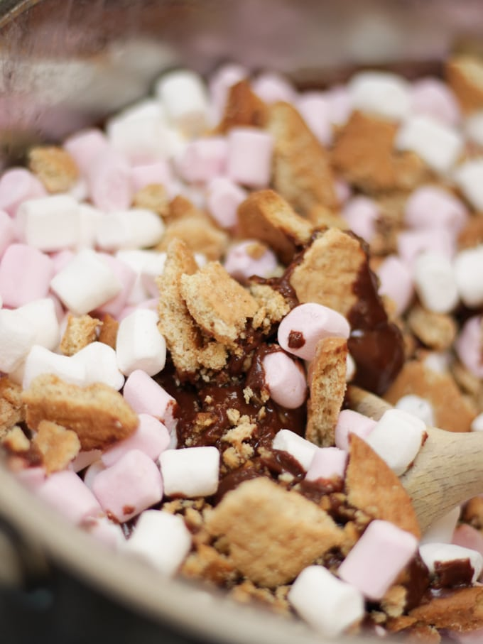Saucepan with melted chocolate, crushed biscuits and marshmallows for Rolo Rocky Road recipe.