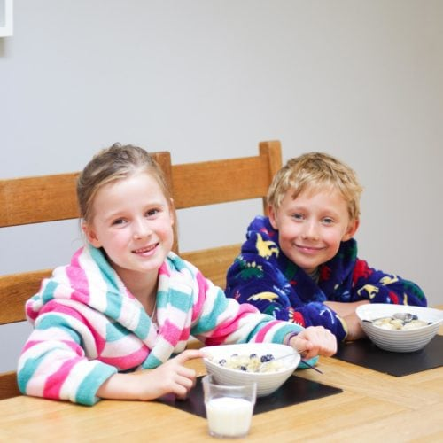 Girl and boy in dressing gowns as table eating porridge.
