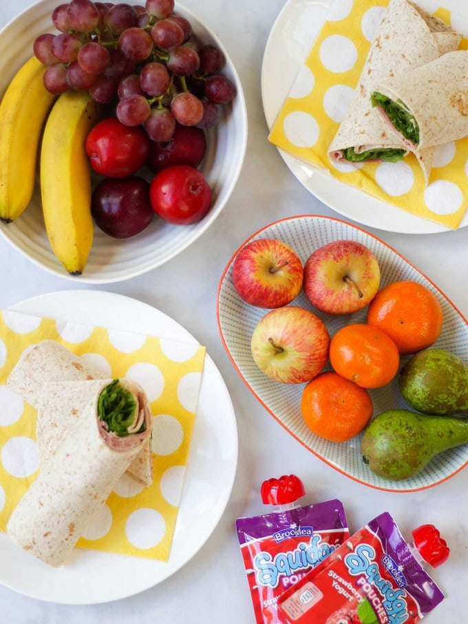 Wraps and fruit on a white background for back to school routine post.