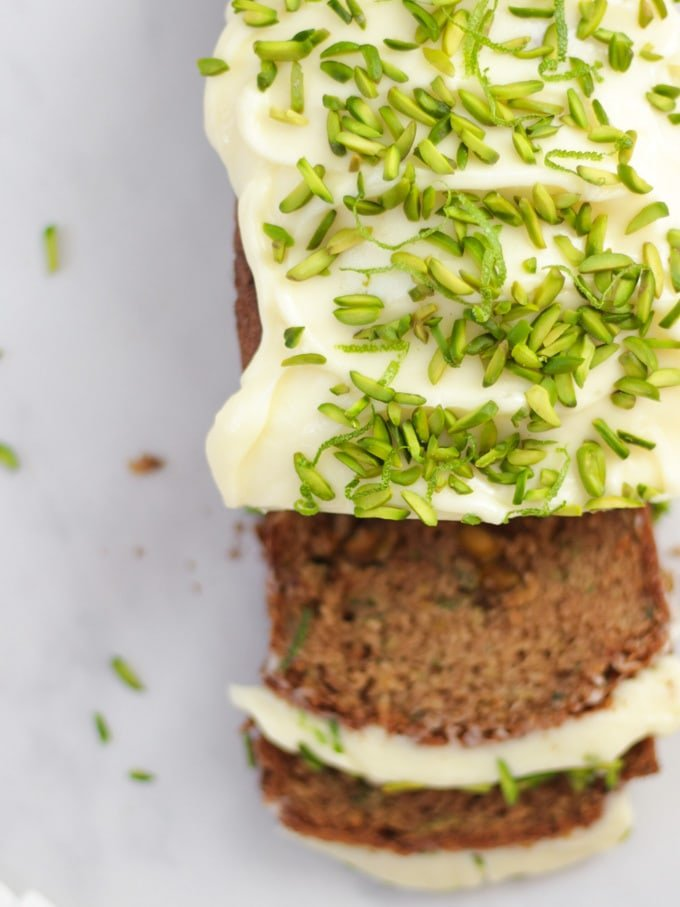 Overhead photo of baked courgette cake loaf topped with cream cheese icing and pistachio nut slices on white marble background.