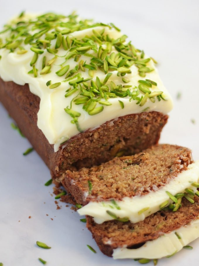 Side angle photo of baked courgette cake loaf topped with cream cheese icing and pistachio nut slices on white marble background.