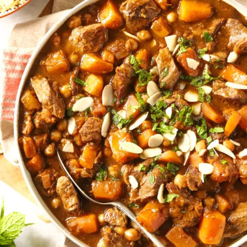 Easy lamb tagine in a dish with spoon, sprinkled with almonds and mint