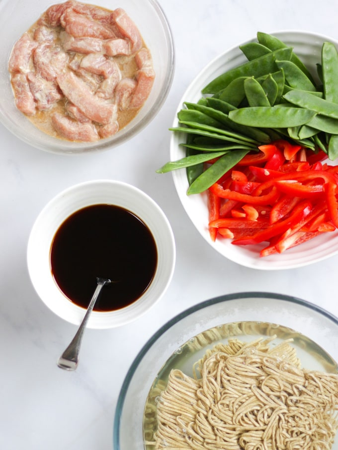 Overhead shot of pork strips, mange tout, red peppers, noodles and soy sauce and oyster sauce on white marble background for pork stir fry recipe.