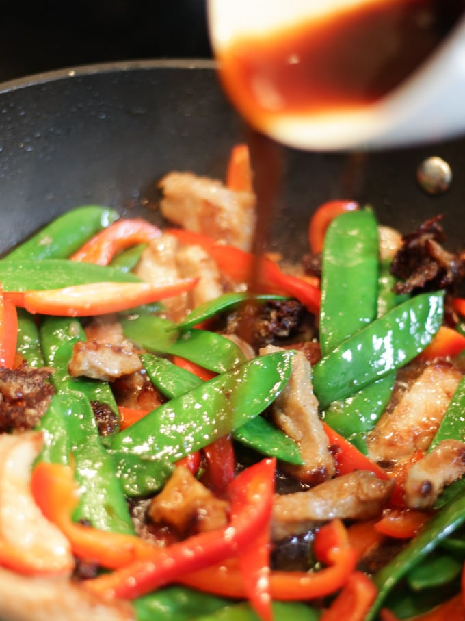 Pork stir fry recipe in wok with sauce being poured in.