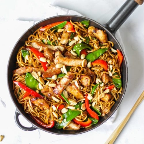 Overhead photo of pork stir fry recipe with noodles, pork, red peppers and mange tout and peanuts.