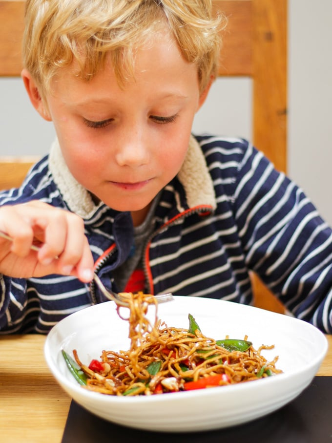 Boy eating pork stir fry with noodles in a white bowl with fork.