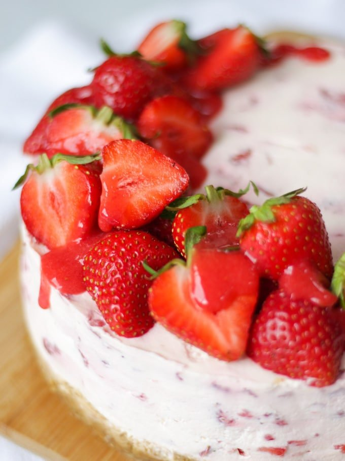 Close up of strawberry cheesecake top with halves strawberries and strawberry coulis drizzle