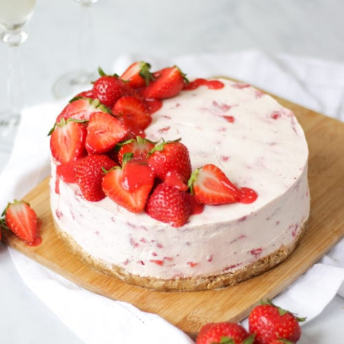 Side angle photo of strawberry cheesecake top with halves strawberries and strawberry coulis drizzle on wooden board and white marble background
