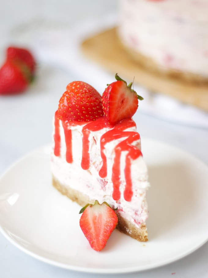 Close up of slice of strawberry cheesecake with Prosecco with strawberry coulis drizzle on a white plate with cheesecake in the background on white marble surface.
