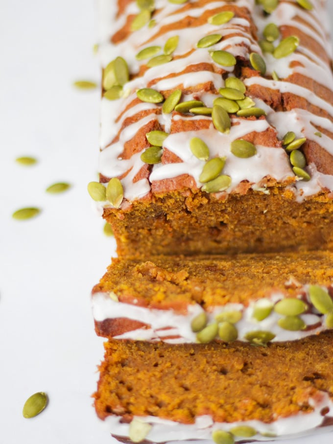 Side angle photo of a pumpkin spice loaf, pumpkin loaf cake, sprinkled with white drizzle icing and pumpkin seeds.