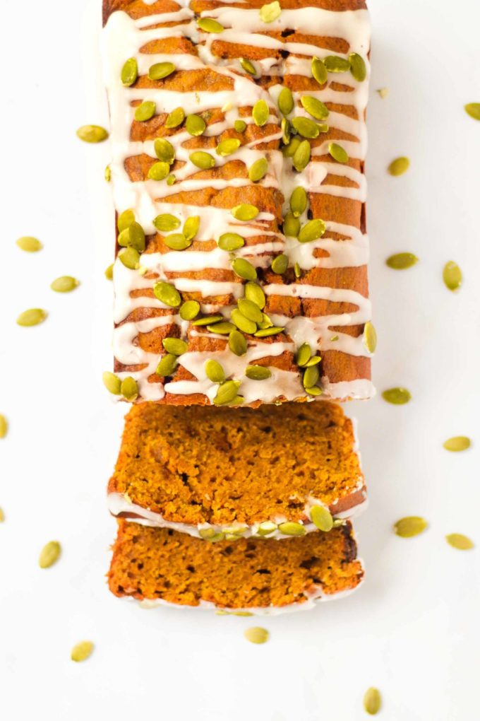 Overhead photo of a pumpkin spice loaf, pumpkin loaf cake, sprinkled with white drizzle icing and pumpkin seeds.