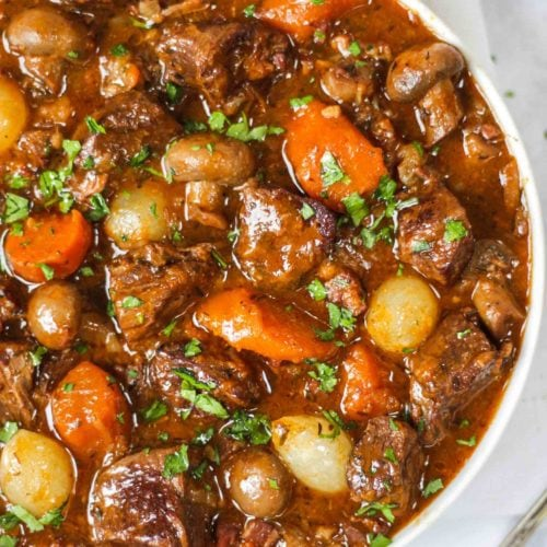 Overhead photo of white bowl of beef bourguignon recipe with beef, carrots, pearl onions and mushrooms showing on white background.
