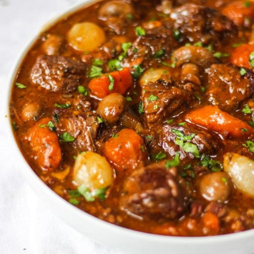 Side photo of white bowl of beef bourguignon recipe with beef, carrots, pearl onions and mushrooms showing on white background.