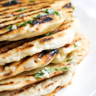 Pile stack of homemade easy three ingredient yoghurt soft flatbreads with griddle lines, garlic butter with parsley on and white plate.