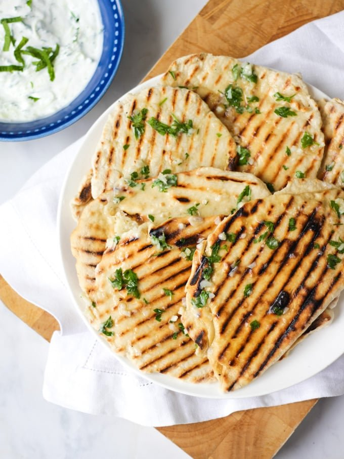 Photo of a plate of flatbreads with griddle lines, on a white plate with white napkin and wooden board, marble background and tzatziki dip in a blog bowl.