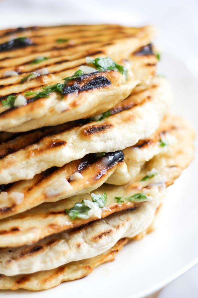 Really easy to make soft Flatbread. Just 3 ingredients, no yeast, cooked in 5 minutes. Served with homemade tzatziki and dripping with garlic butter. These homemade flatbread can also be turned into pizzas with toppings, used for sandwiches or as a replacement for naan breads. #tamingtwins #flatbread #flatbreadrecipe #flatbreads #yeastfreebread #easyrecipe #greekfood #indianfood #garlic #tzatziki #kidscooking