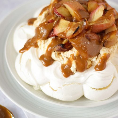 Salted caramel and apple pavlova on a white plate on white background piled with apples.