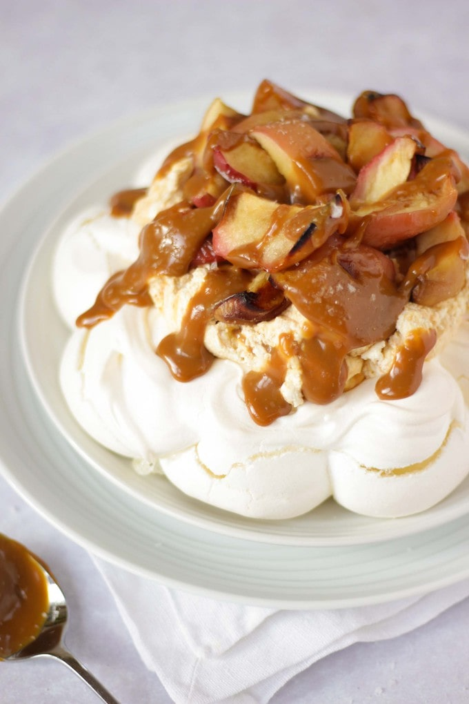 Want to learn how to make a pavlova? Here's a simple recipe for an easy and delicious Salted Caramel & Apple Autumn Pavlova dessert.With salted caramel sauce and caramelised, oven roasted apples. #tamingtwins #pavlova #saltedcaramel #autumnfood #autumndessert #dessertrecipe