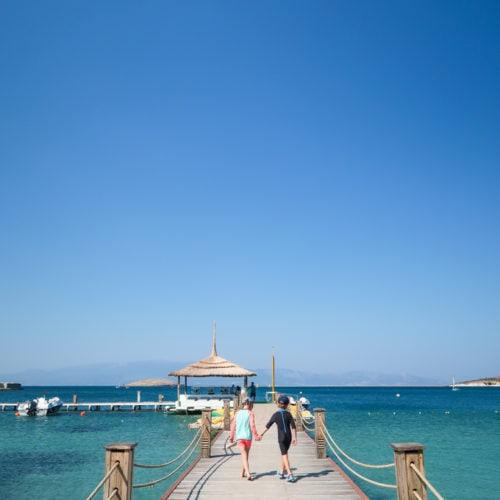 Girl and boy on jetty backs to camera at Phokaia restort in Turkey Mark Warner.