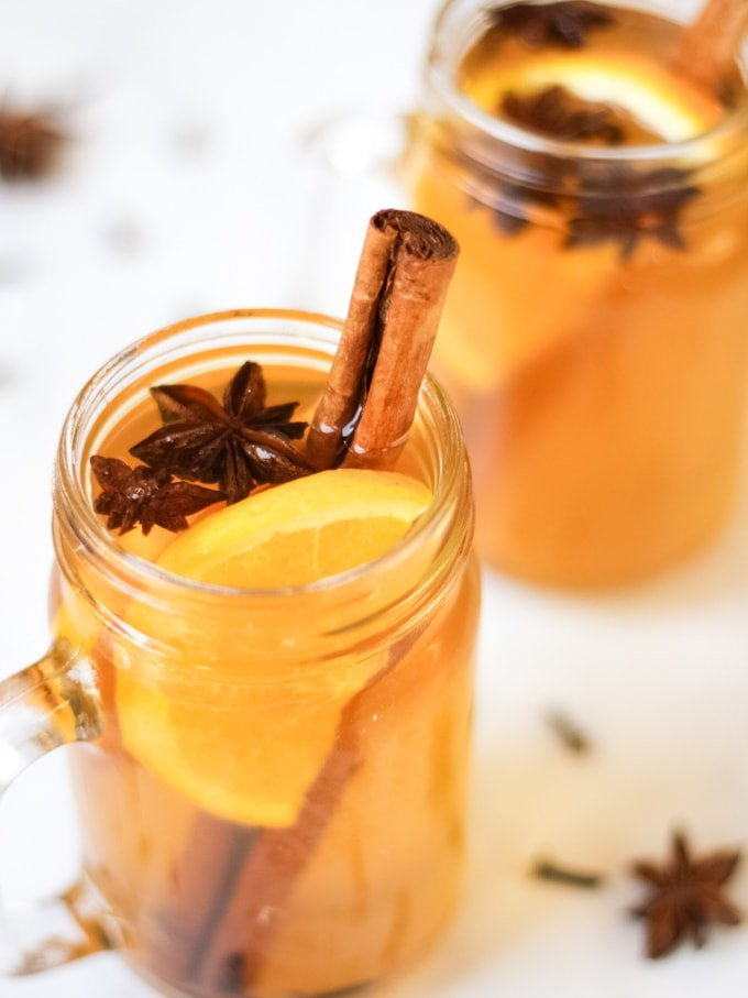 Glass mugs of spiced apple juice recipe with slices of orange, cinnamon sticks, star anise and cloves.