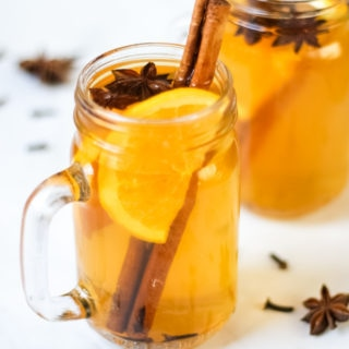 Overhead photo of two glass mugs of slow cooker mulled cider recipe on a white background, with slices of orange, cinnamon sticks, star anise and cloves.