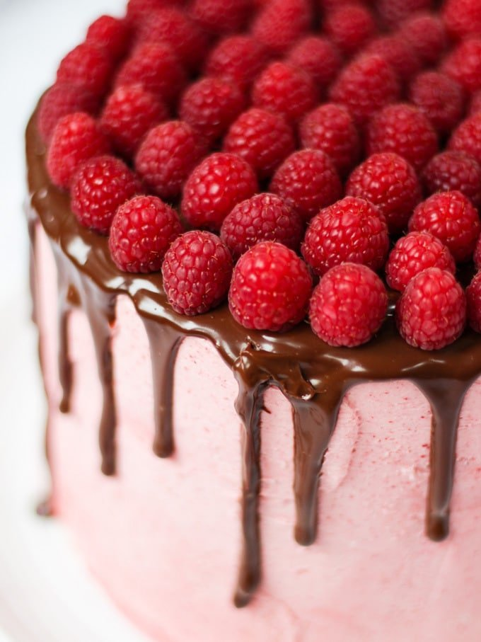 Raspberry cake on white plate on white marble background with chocolate ganache and fresh raspberries on top.