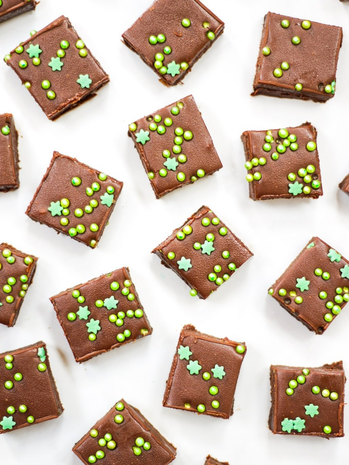 Overhead photo of baileys fudge made with easy microwave recipe on white marble background with green sprinkles.