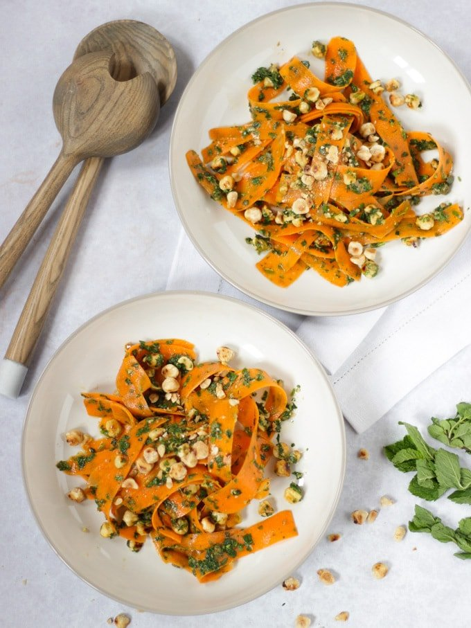 Two bowls of carrot salad with wooden salad serves and white napkin.