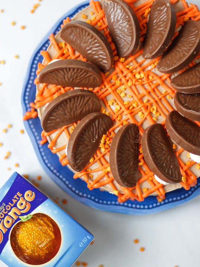 Overhead photo of a No Bake Terry's Chocolate Orange Cheesecake on a blue plate with a chocolate orange in a box in the background, drizzled with white chocolate coloured orange for this dessert recipe.