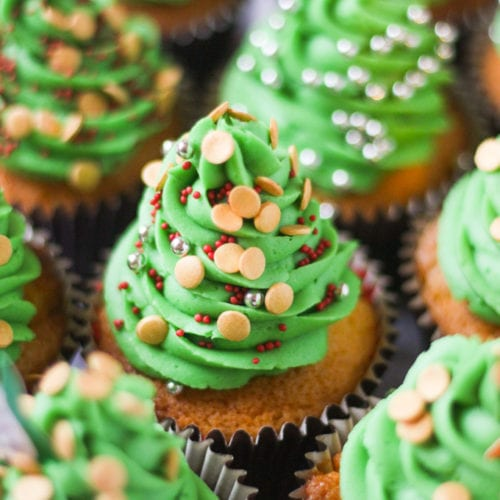 Side photo of green iced Christmas tree cupcakes with sprinkles.