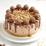 Side angle photo of a no bake Ferrero richer cheesecake recipe on a white plate with Ferrero richer and gold sprinkles on top with dropped chocolate.