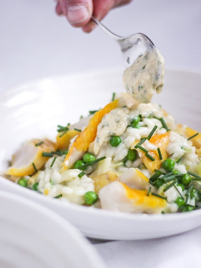 The Saucy Fish Co Smoked Haddock recipe for Smoked Haddock Risotto in bowl with spoon dropping sauce on top topped with chives.