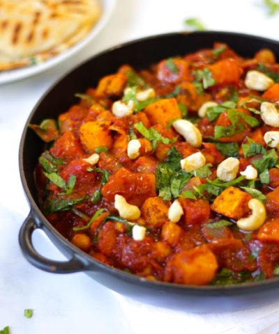 Butternut squash curry sprinkled with coriander in a black cast iron pan with cashew nuts on top on a white marble background with a plate with some flatbreads on too.