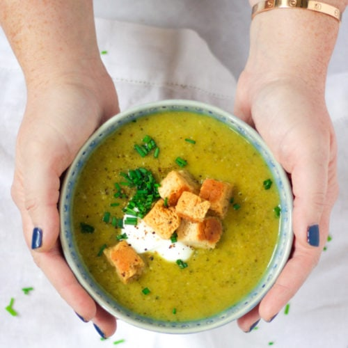 Overhead angle photo of a blue bowl of courgette soup recipe being held in hands topped with creme fraiche, bread croutons and chives on white background.