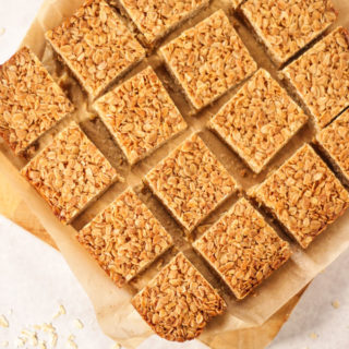 Pieces of square flapjack on top of baking paper on a wooden board and white background with sprinkled oats.