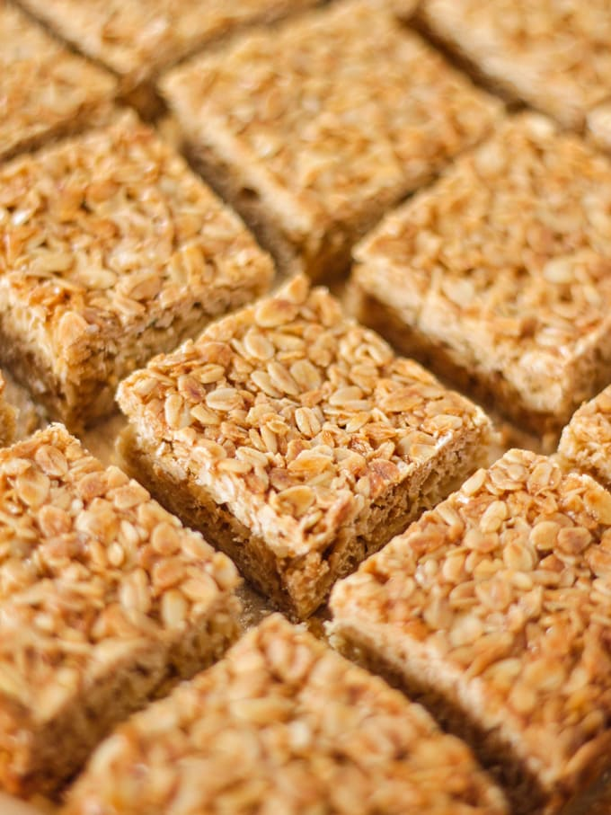 Pieces of square flapjack from a side angle on top of baking paper.